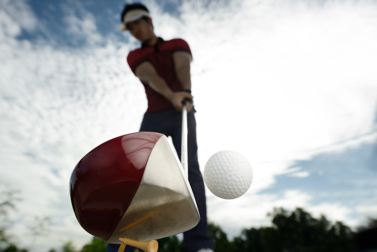 man using illegal golf driver to hit the golf ball
