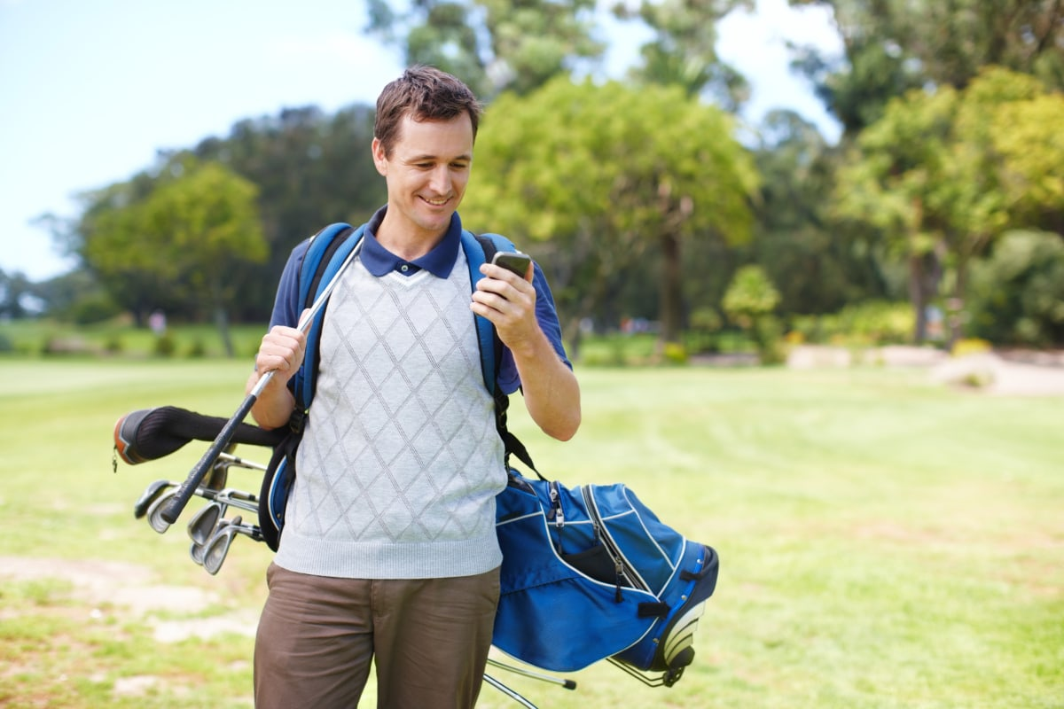 man looking at mobile phone about his golf score