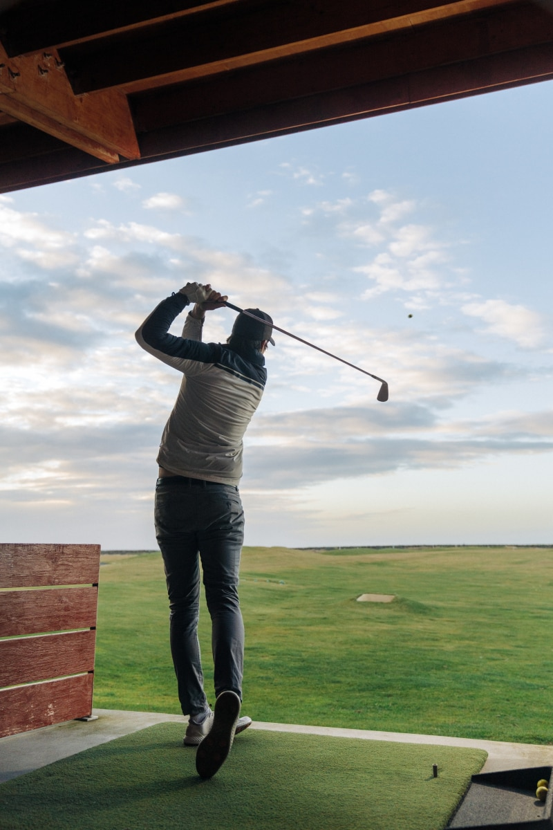 golfer practicing in a driving range in winter